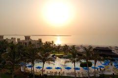 Solnedgång och stranden av det lyxiga hotellet arkivbilder
