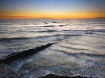 Solnedgång och tidvattnet Royaltyfria Bilder