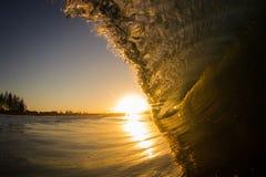 Solnedgång och vågen Arkivbilder