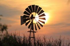 Solnedgång och Windpumps - Afrika Arkivbild
