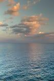 Solnedgång oklarheter över havet Royaltyfria Bilder
