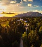 Solnedgång ovanför en liten by som lokaliseras i höga Tatra berg arkivbilder