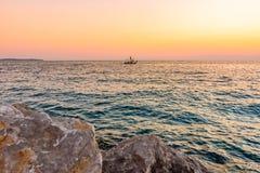 Solnedgång ovanför fartyget på Adriatiskt havet Magiskt mjukt ljus och blått vatten nära den Piran staden, Slovenien Stenen vagga arkivfoto