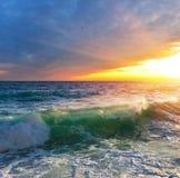 Solnedgång ovanför havet med den genomskinliga vågen royaltyfria bilder