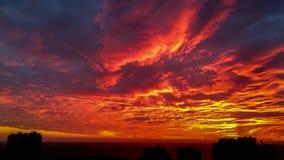 Solnedgång ovanför kontur av cityscapebyggnader Fotografering för Bildbyråer