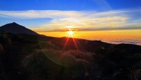 Solnedgång ovanför molnen som silhouetting den Teide vulkan Arkivbilder