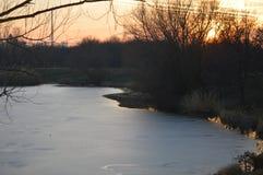 Solnedgång ovanför sjön på slutet av vintern royaltyfria bilder