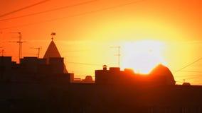 Solnedgång ovanför stadsbyggnadstaket arkivfilmer