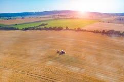 Solnedgång ovanför traktoren som arbetar på vetefältet Royaltyfria Foton