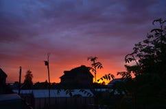 Solnedgång på bakgrunden av ett landshus royaltyfria bilder