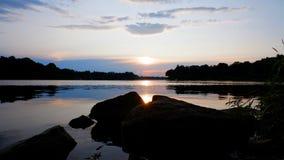 Solnedgång på banken av en flod royaltyfria bilder