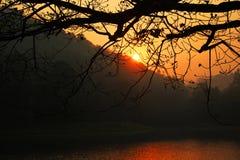 Solnedgång på bergen som reflekterar sjön royaltyfria bilder