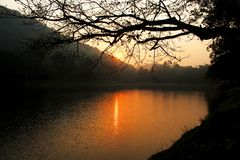 Solnedgång på bergen som reflekterar sjön arkivbilder