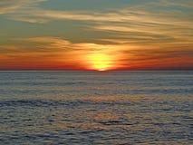 Solnedgång på Blacket Sea, solen och de härliga färgrika molnen Royaltyfri Foto