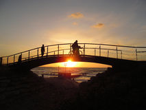 Solnedgång på bron vid havet Arkivfoton