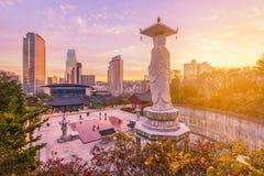 Solnedgång på den Bongeunsa templet av i stadens centrum horisont i den Seoul staden, Sydkorea Royaltyfri Bild