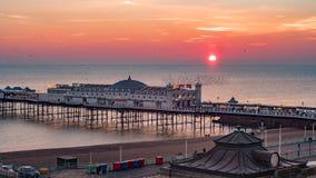 Solnedgång på den Brighton pir med en flock av fåglar Arkivbild