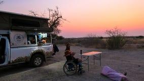 Solnedgång på den centrala Kalahari leken Reseve med en person i den royaltyfri fotografi