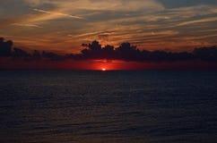 Solnedgång på den guld- sandstranden Arkivbild