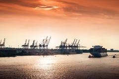 Solnedgång på den Hamburg hamnen Arkivfoto