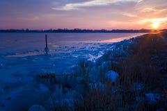 Solnedgång på den iskalla sjön Arkivbild
