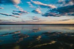 Solnedgång på den lugna sjön Arkivfoto