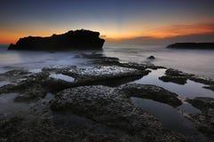 Solnedgång på den Melasti stranden i bali indonesia Royaltyfri Foto