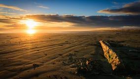 Solnedgång på den Oreti stranden Arkivfoto