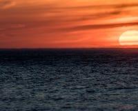 Solnedgång på den ovala stranden Royaltyfri Bild