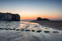 Solnedgång på den Perranporth stranden Arkivbilder