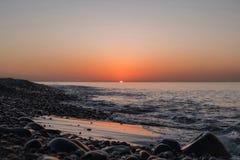 Solnedgång på den sandiga och steniga stranden arkivfoto