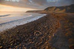 Solnedgång på den sceniska Palliser fjärdkustlinjen, Wairarapa, Nya Zeeland Royaltyfria Foton