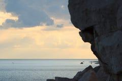 Solnedgång på den steniga kustlinjen Arkivfoto