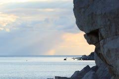 Solnedgång på den steniga kustlinjen Royaltyfri Bild