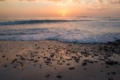 Solnedgång på den steniga stranden Fotografering för Bildbyråer