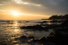 Solnedgång på den steniga stranden Royaltyfria Foton
