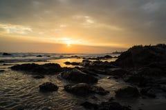 Solnedgång på den steniga stranden Arkivbild