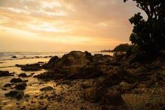 Solnedgång på den steniga stranden Arkivfoton