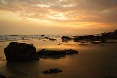 Solnedgång på den steniga stranden Arkivfoto