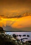 Solnedgång på den steniga stranden Royaltyfria Bilder