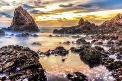 Solnedgång på den steniga stranden med den dimmiga vågen Royaltyfri Foto