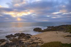 Solnedgång på den steniga stranden mellan molnen arkivfoton