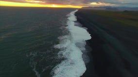 Solnedgång på den svarta stranden av Island arkivfilmer