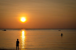 Solnedgång på den tropiska stranden med konturer arkivfoto