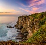 Solnedgång på den Uluwatu klippan Arkivfoto