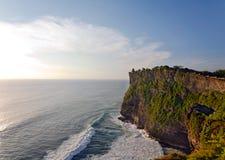 Solnedgång på den Uluwatu templet överst av stora klippor Arkivbilder