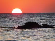 Solnedgång på den vita stranden Puerto Galera arkivbilder