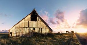 Solnedgång på en övergiven ladugård, färgbild Arkivfoto