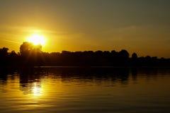 Solnedgång på en flodlandskapkontur med reflexionen av suen Royaltyfria Foton