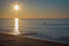 Solnedgång på en sandig strand med en skeppsdocka royaltyfria foton